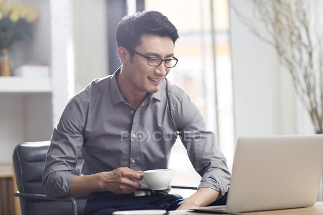 Asiatischer Mann Mit Laptop Und Kaffee Im Buro Arbeiten Geschaft