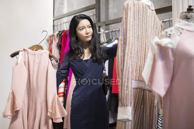 Asian woman choosing clothes in boutique — Stock Photo