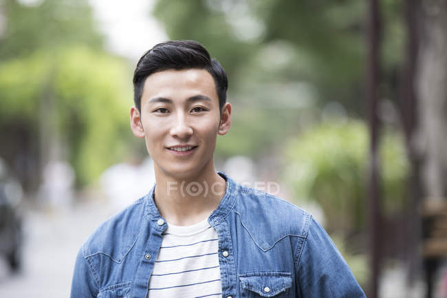 Portrait of young Chinese man looking in camera outdoors — Stock Photo