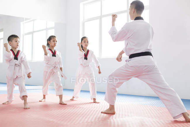 Chinese children practicing Taekwondo stance with instructor — Stock Photo