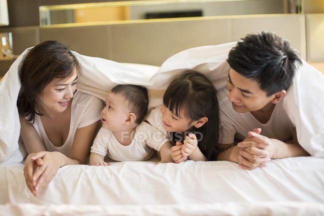 Familia China acostado en cama debajo de la manta - foto de stock