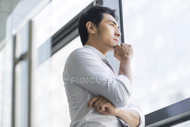 Pensive Chinese businessman looking through window — Stock Photo