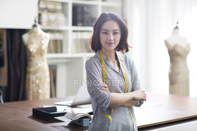 Female asian fashion designer in studio with crossed arms — Stock Photo