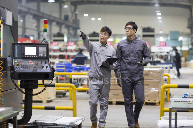 Confident Chinese engineers inspecting industrial factory with digital tablet — Stock Photo