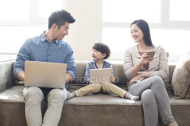 Chinese family with child using digital gadgets on sofa — Stock Photo
