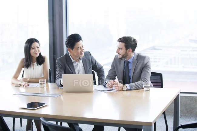 Uomini d'affari che parlano in sala riunioni — Foto stock