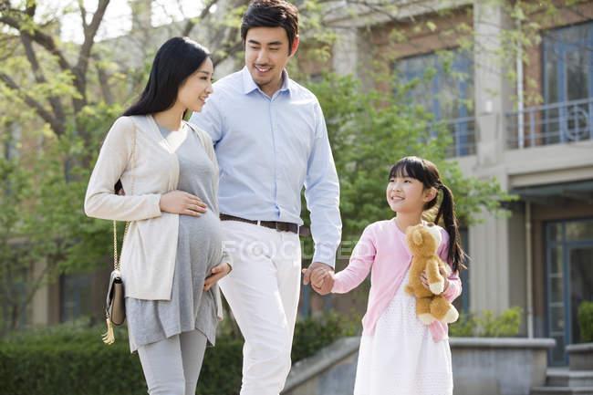 Asiatische Familie hält Händchen, während sie auf der Straße läuft — Stockfoto