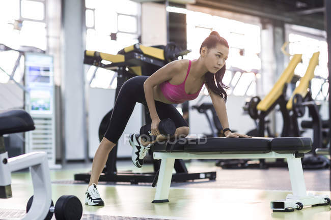 Chinese woman exercising at gym with dumbbell — Stock Photo