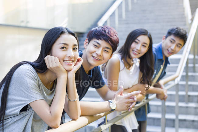 Chinese woman standing together with friends on stairs — Stock Photo