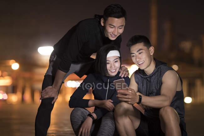 Atleti cinesi che utilizzano smartphone in strada — Foto stock