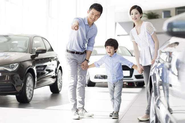 Chinese family in car dealership showroom pointing on car — Stock Photo