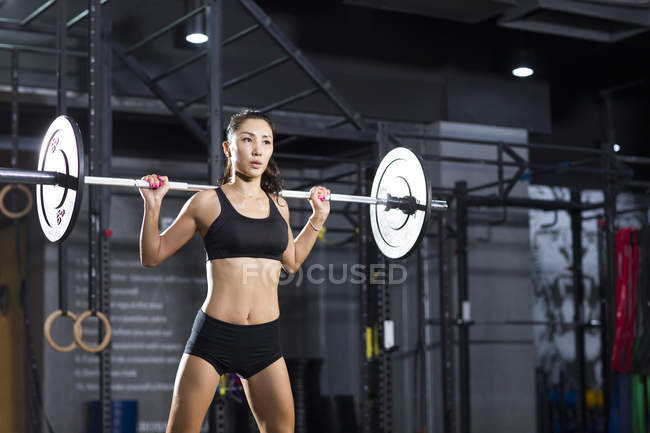 Chinesische Sportlerin heben Langhantel in Turnhalle — Stockfoto