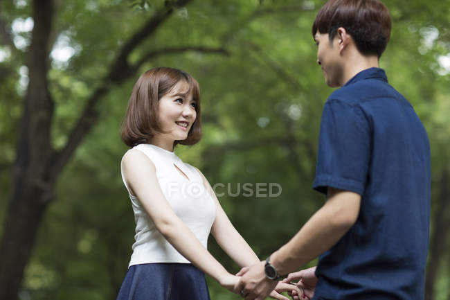 Young Chinese couple holding hands in park — Stock Photo