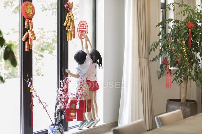 Дети, украшающие окна с Китайский Новый год вырезки — стоковое фото