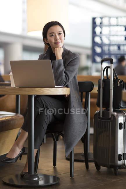 Азиатка ждет в аэропорту с ноутбуком — стоковое фото