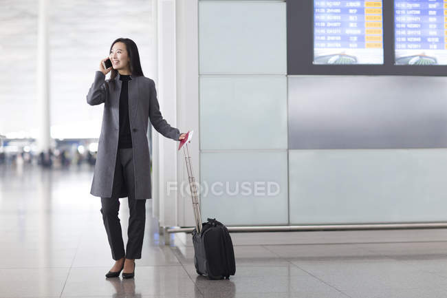 Asian woman talking on phone at airport with baggage — Stock Photo