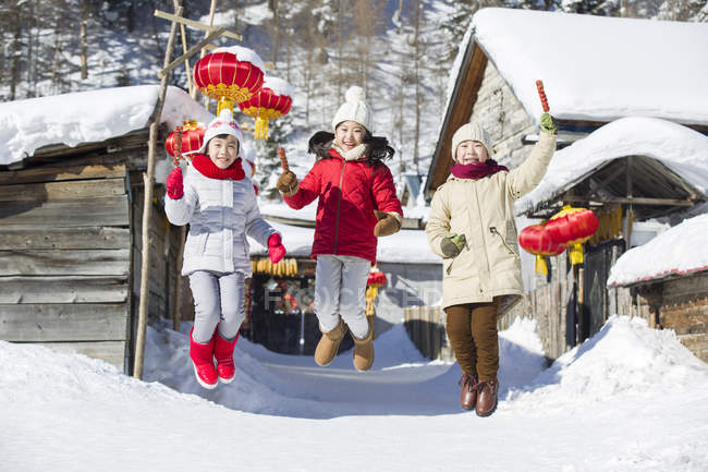 Chinese children jumping with candied haws at village festival — Stock Photo