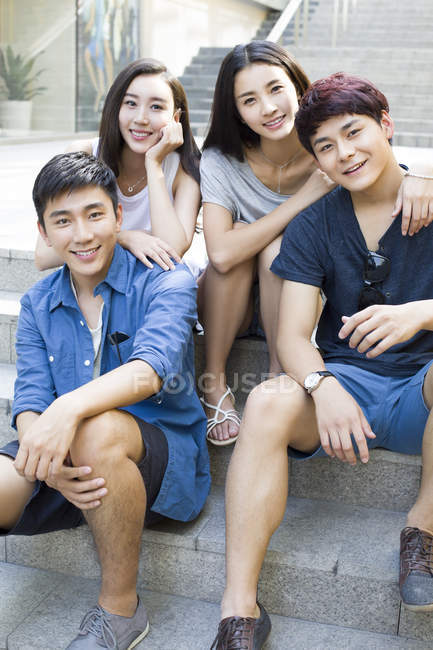 Chinese friends on street stairs and looking in camera — Stock Photo
