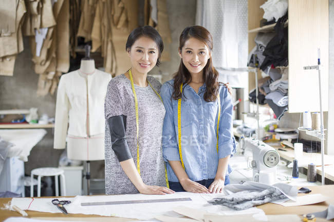 Chinese female fashion designers standing at table — Stock Photo