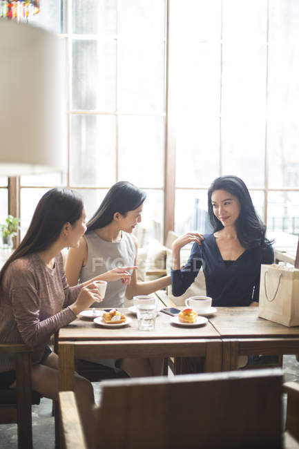 Chinese woman demonstrating new clothing to female friends in coffee shop — Stock Photo