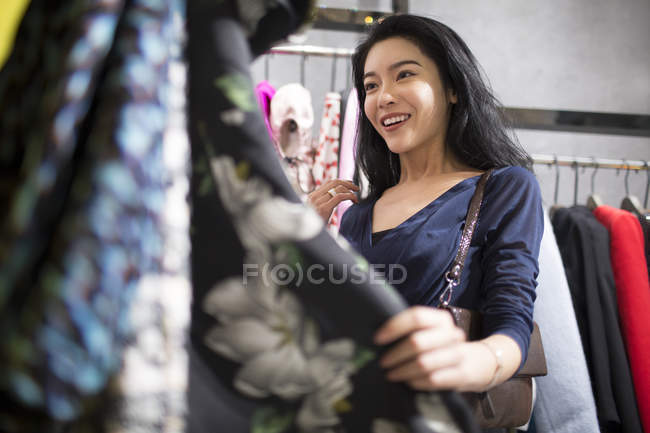 Asian woman shopping in clothing store — Stock Photo