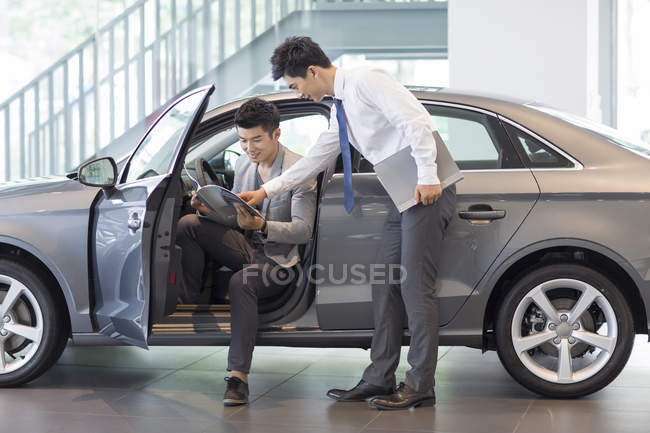 Man choosing car in showroom with dealer — Stock Photo