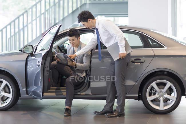 Man choosing car in showroom with dealer — Stock Photo