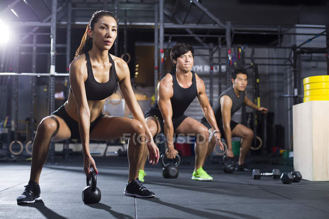 Chinese athletes training with kettlebells in crossfit gym — Stock Photo