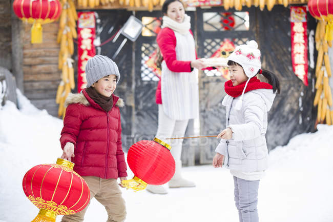 Children playing with Chinese lanterns with mother in background — Stock Photo