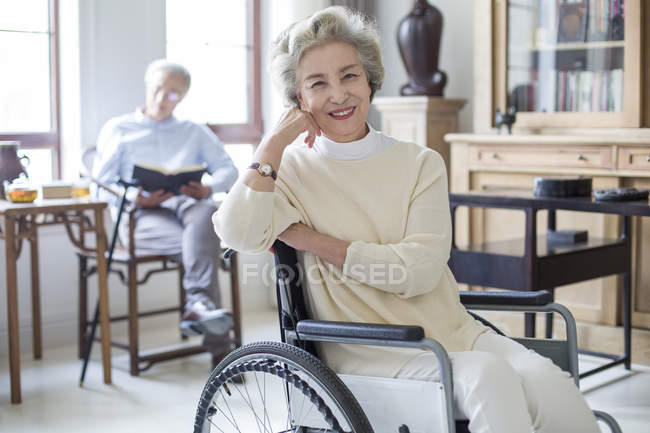 Senior Chinese woman sitting in wheelchair with man reading in background — Stock Photo