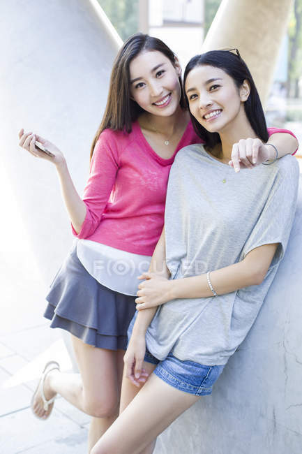 Chinese female friends embracing and posing on street — Stock Photo
