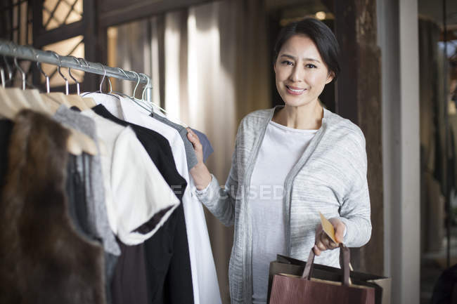 Mature chinese woman with credit card in clothing store — Stock Photo