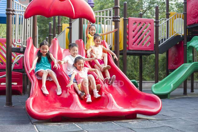 Niños chinos deslizándose en el parque de atracciones - foto de stock