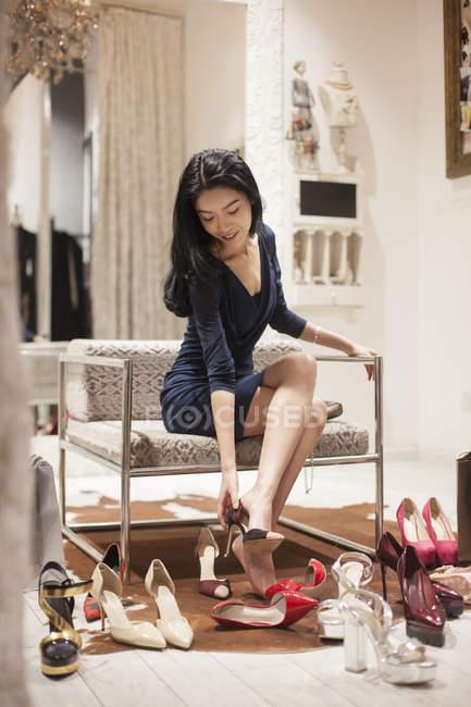 Mujer China probandose zapatos en tienda — diseño, ir de