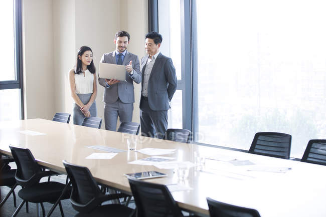 Les hommes d'affaires utilisant un ordinateur portable dans la salle de réunion — Photo de stock