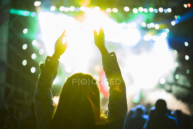 Female silhouette with arms raised at music concert — Stock Photo