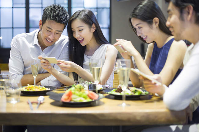 Asian friends taking photos of food while dinner in restaurant — Stock Photo