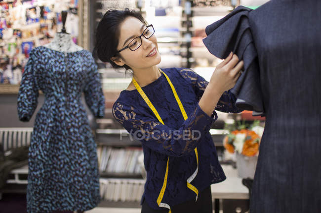 Chinese female fashion designer working on dress in store — Stock Photo