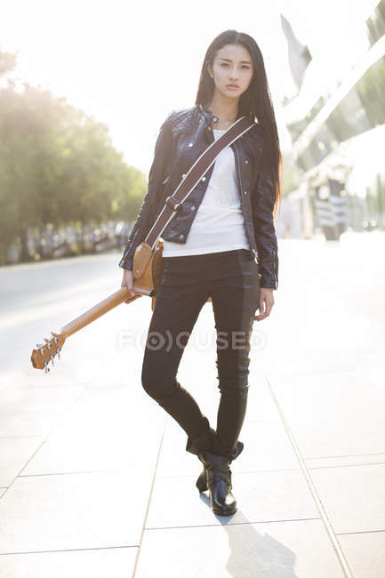 Chinese female guitarist standing with guitar on street — Stock Photo