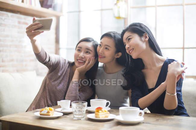 Chinoise amies prendre selfie dans café — Photo de stock