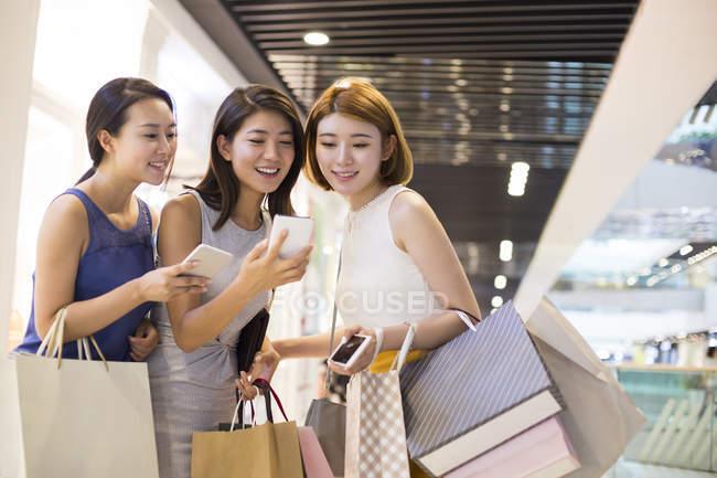 Amici di sesso femminile utilizzando smartphone durante lo shopping — Foto stock