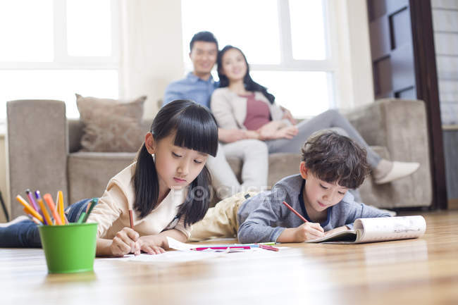 Asian siblings studying together at home while parents watching — Stock Photo