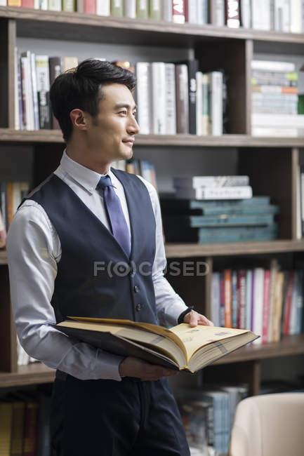 Asiatische Geschäftsmann Lesebuch in Studie — Stockfoto