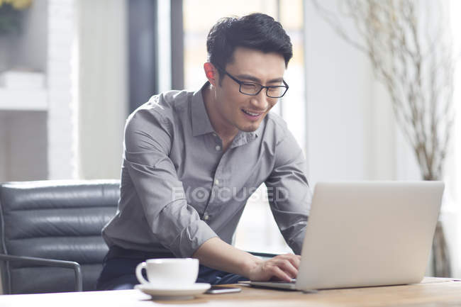 Asiatischer Mann Mit Laptop Im Buro Arbeiten Geschaft Lachelnd