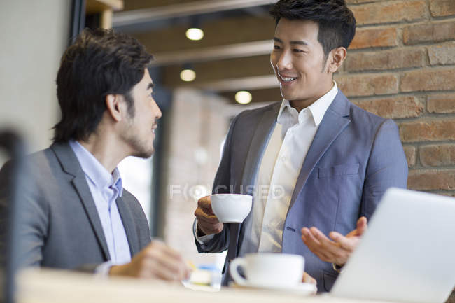 Asian men discussing business in cafe — Stock Photo