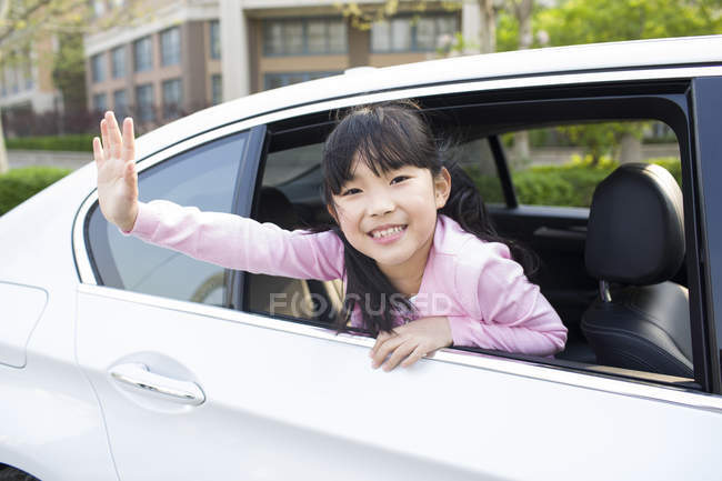 Asian girl leaning out of car window and waving — Stock Photo