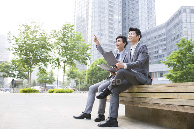 Chinese businessmen working with laptop on street — Stock Photo