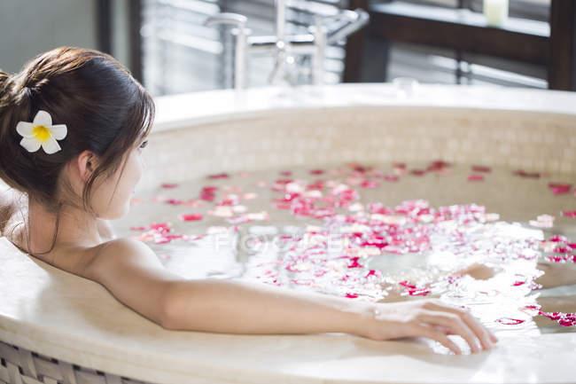 Vasca Da Bagno Rosa : Giovane donna cinese nella vasca da bagno con petali di rosa