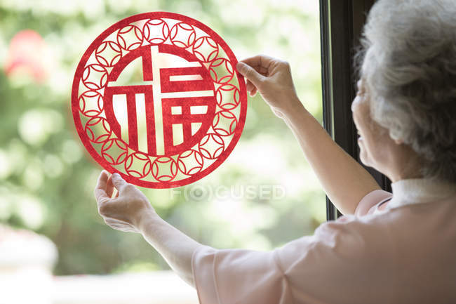 Senior woman with Chinese New Year paper-cut — Stock Photo