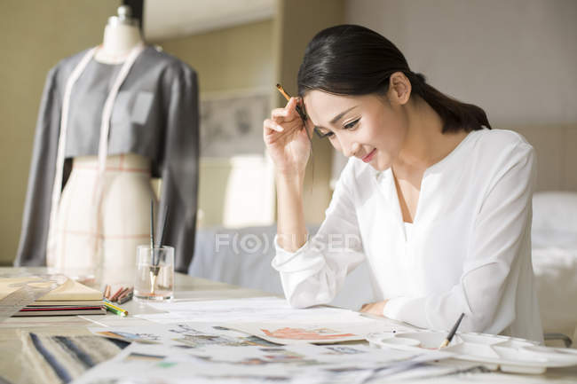 Chinese fashion designer working on sketch — Stock Photo